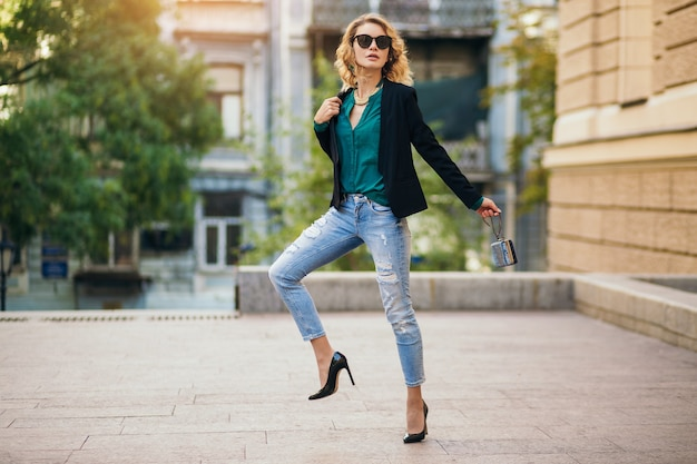 Attraente donna elegante che cammina per una strada cittadina con scarpe col tacco alto, jeans blu wesaring, giacca nera, camicetta verde, occhiali da sole, borsetta con in mano, tendenza della moda dell'estate, bella signora magra