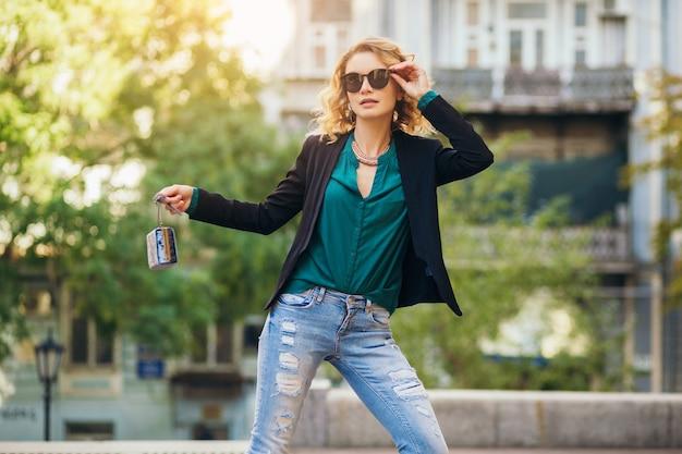 자신감과 섹시, 검은 재킷을 입고 지갑과 도시 거리에서 산책하는 매력적인 우아한 여자,