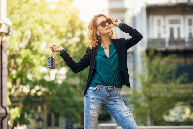 財布を持って街を歩いて、黒いジャケットを着て、自信を持ってセクシーな魅力的なエレガントな女性、