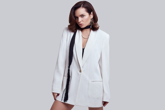 Attractive elegant woman with dark hair in fashion white suit