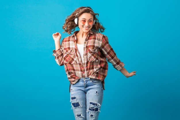 Attractive emotional woman jumping with funny crazy face expression in checkered shirt and jeans isolated on blue studio background, wearing pink sunglasses