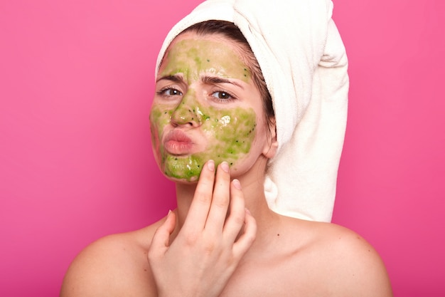 Attractive emotional young beauty has green mask on her face, day to have spa procedures, protrudes her lips, has unpleasant facial expression. magnetic model poses isolated on pink.