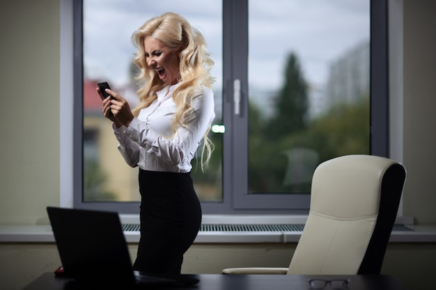 Attractive employee in the office uses a smartphone near the window
