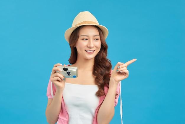 青いスタジオの背景に分離されたセマラを喜んで保持している魅力的なエネルギッシュなアジアの女性