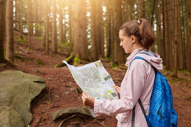両手で地図を持ち、地図を注意深く見て、森で迷子になり、オリエンテーションスキルを向上させる魅力的なエネルギッシュな若い女性