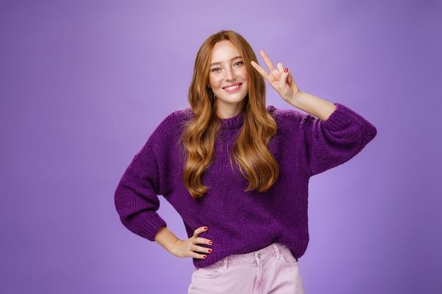 Привлекательная энергичная рыжая женщина в фиолетовом свитере показывает жест победы возле глаза и широко улыбается, наклоняя голову, довольная и радостная, держа руку на талии, позирует на фиолетовом фоне.