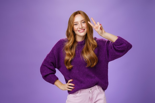Attractive energized redhead woman in purple sweater showing victory gesture near eye and smiling broadly tilting head satisfied and joyful, holding hand on waist posing over violet background.