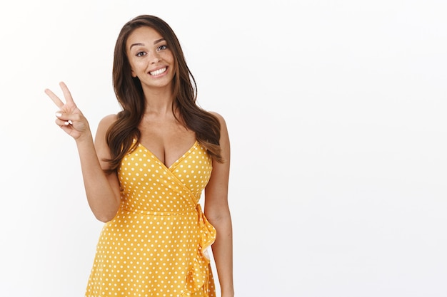 Attraente donna carina entusiasta in abito estivo giallo, data di travestimento, mostra segno di pace o vittoria, sorridente tenera e ottimista, goditi le vacanze