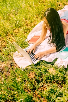 Attractive ethnic female using laptop in meadow