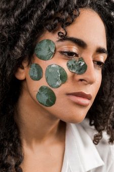 Attractive ethnic woman with wet leaves on face