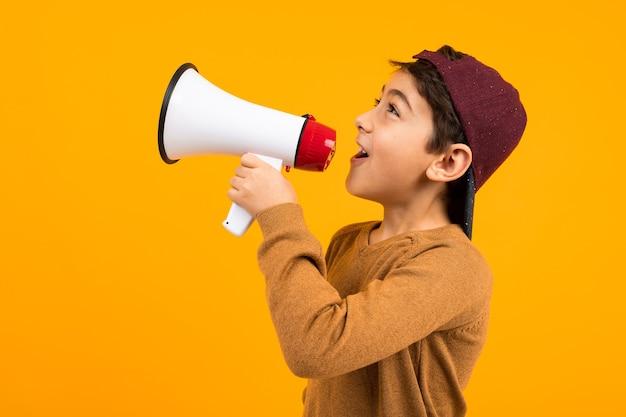 オレンジ色のスタジオの背景にポスターのためにメガホンでニュースを叫んでいる魅力的なヨーロッパの少年。