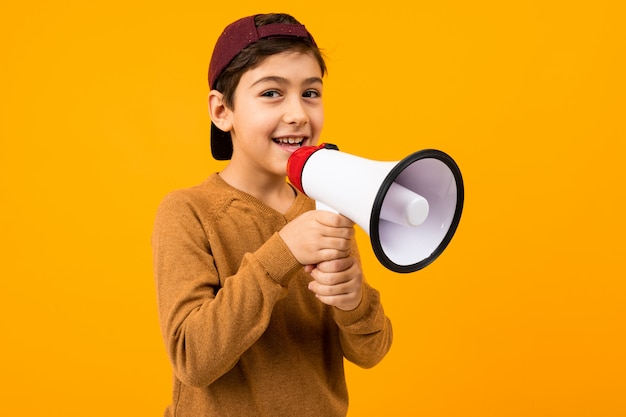Attractive european boy with a megaphone in his hands for a poster onn orange