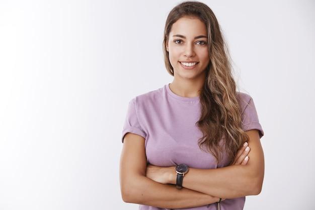 보라색 티셔츠를 입은 매력적인 유럽 곱슬머리 여성은 자신감 있는 가슴 위로 팔짱을 끼고 활짝 웃고, 목표를 달성할 준비가 되어 있다고 느끼는 활동적인 생활 방식을 이끌고, 자신감 넘치는 미소를 짓습니다.