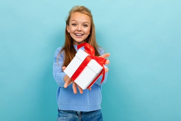 Attractive european girl holding a gift on a light blue