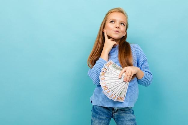 Attractive european girl holding money in hands on light blue