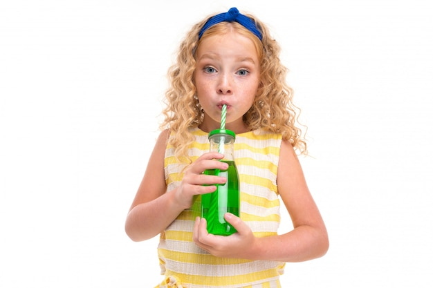 Attractive european girl is drinking something from a glass on white