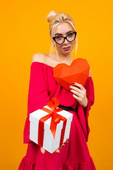 Attractive european girl in red dress holds gift box and red paper heart on orange studio space