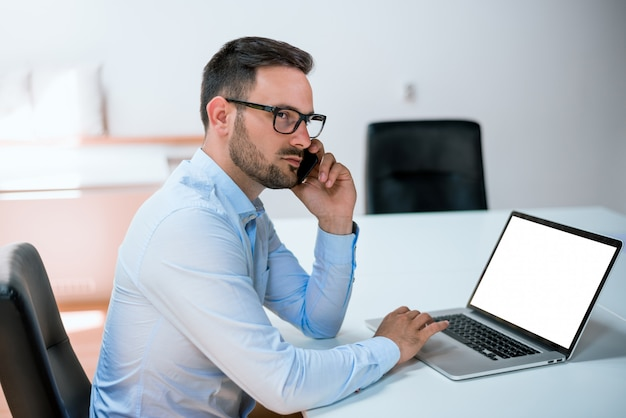 Attractive european guy talking on phone while using laptop at workplace