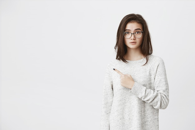 Attractive european model pointing index finger aside with half-opened mouth, expressing curiosity and wonder, wearing glasses and trendy shirt..