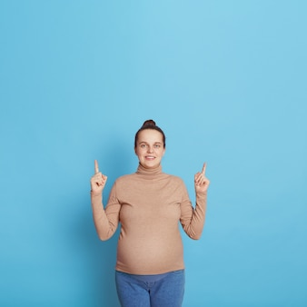 Attraente donna incinta europea che punta il dito verso l'alto con entrambi gli indici che indossano abbigliamento casual, indicando qualcosa sopra la sua testa, copia spazio per le promozioni.