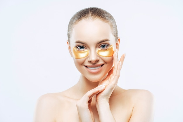 Attractive european woman touches face gently, smiles tenderly, applies golden hydrogel patches under eyes