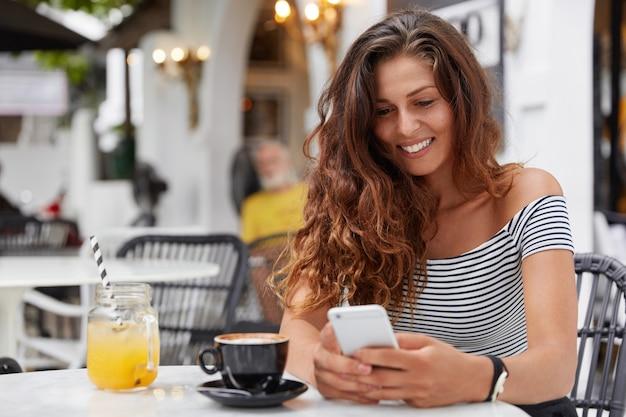 행복한 표정으로 매력적인 유럽 여성은 아늑한 커피 숍에서 현대적인 휴대 전화를 사용합니다.