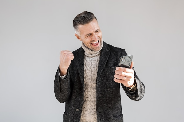 Attractive excited man wearing coat standing isolated over gray wall, using mobile phone, celebrating