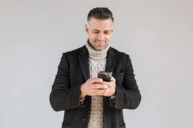 Attractive excited man wearing coat standing isolated over gray wall, using mobile phone