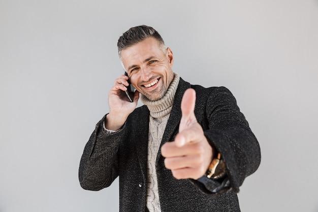 Привлекательный возбужденный мужчина в пальто, стоящий изолированно над серой стеной, разговаривает по мобильному телефону, указывая пальцем вперед