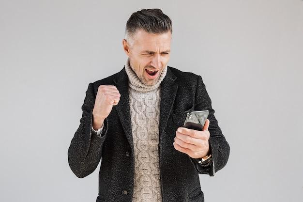 Привлекательный возбужденный мужчина в пальто, стоящий изолированно над серой стеной, используя мобильный телефон, празднует