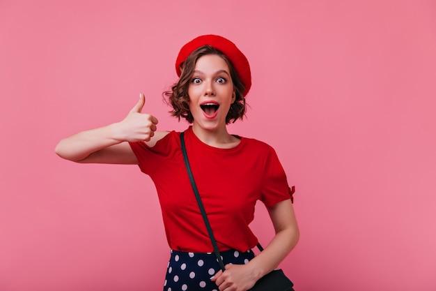 親指を立ててポーズをとる魅力的な興奮した女性。トレンディな赤いベレー帽の陽気なフランスの女の子の屋内の肖像画。