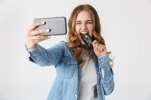 白の上に孤立して立っている魅力的な興奮した若い女の子、自分撮りを取り、プラスチックのクレジットカードを表示