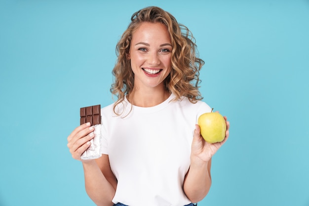 青に孤立して立っているカジュアルな服を着て、リンゴとチョコレートのバーを示す魅力的な興奮した若い女の子