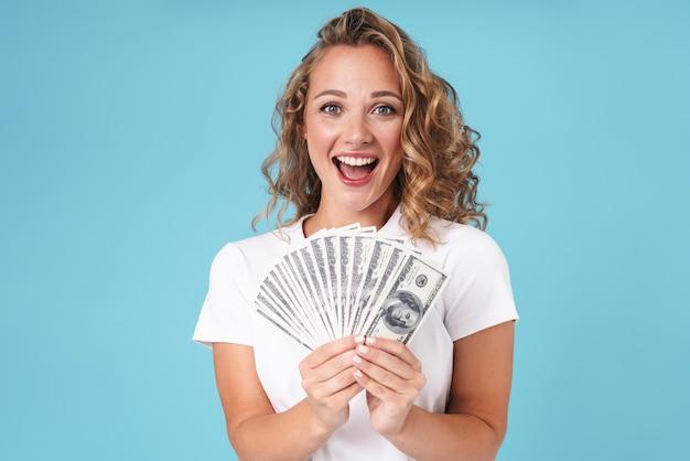 Привлекательная возбужденная молодая девушка в повседневной одежде, стоящая изолирована на синем, показывая денежные банкноты, празднуя