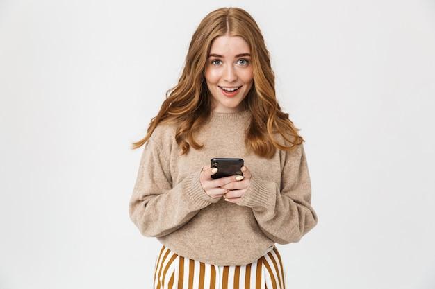 Привлекательная возбужденная молодая девушка в свитере, стоящая изолированно над белой стеной, с помощью мобильного телефона