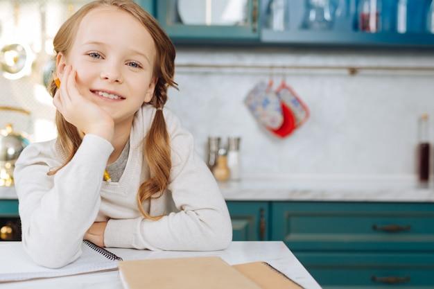 Привлекательная буйная светловолосая девушка улыбается и сидит за столом со своим блокнотом и держит карандаш