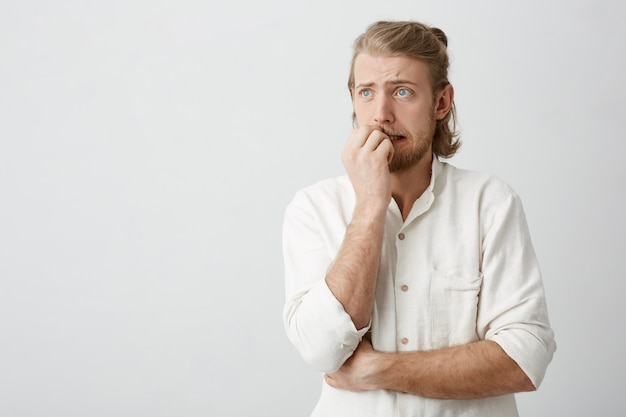 Привлекательный белокурый мужчина с голубыми глазами и бородой грызет ногти