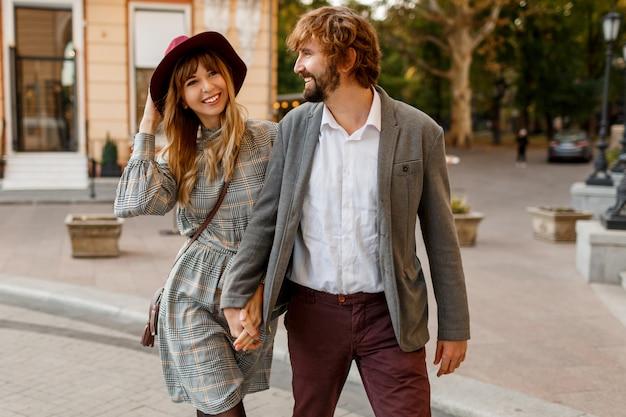 魅力的なファッションのカップルは、晴れた春の古い通りでポーズします。かなり美しい女性と彼女のハンサムなスタイリッシュなボーイフレンドは屋外を抱き締めます。