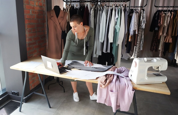Attractive fashion designer with short hair, working in a workshop, atelier standing at a table with a laptop