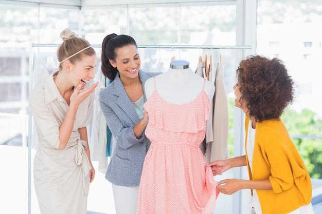 Привлекательные модельеры, смотрящие на платье
