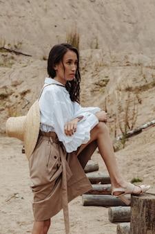 スタイリッシュな衣装で砂の採石場でポーズをとるアメリカンインディアンの外観を持つ魅力的なファッションモデル。