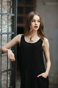 Attraente donna di moda in abito nero in posa vicino al muro bianco