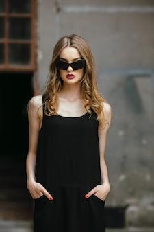 白い壁の近くでポーズをとってサングラスと黒のドレスで魅力的なファッションの女性