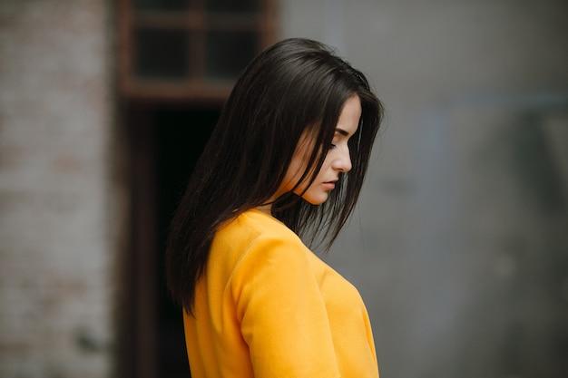 白い壁の近くでポーズをとってオレンジ色のドレスの魅力的なファッションの女性