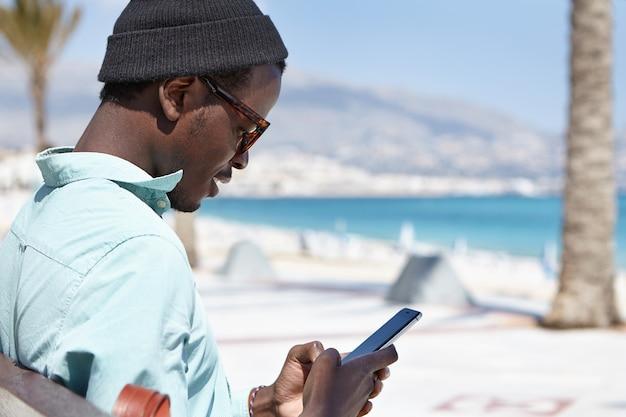 Ragazzo europeo nero alla moda attraente che si distende durante il giorno, seduto su una panchina vicino al mare, tenendo e utilizzando un moderno dispositivo elettronico per il networking, godendo la comunicazione online con gli amici