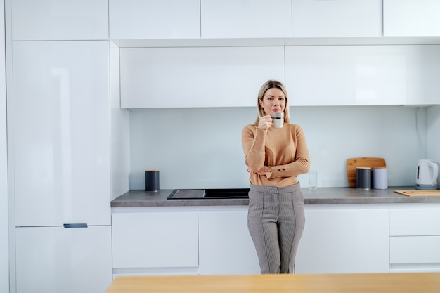 Attractive fashionable caucasian smiling blonde woman leaning on kitchen counter and holding mug with coffee. apartment interior.