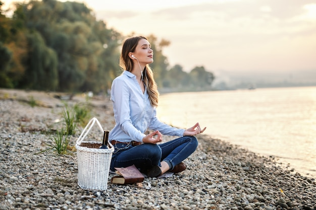 Attractive fashionable caucasian young woman sitting on coast near river, listening music and meditating. next to her is picnic basket.