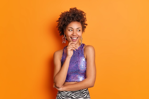 Привлекательная модная кудрявая афроамериканка в стильной одежде, держащая подбородок, с радостью смотрит в сторону, принимает позитивные позы на оранжевом фоне платьев для вечеринки или свидания. концепция стиля