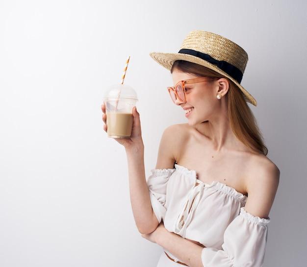 Привлекательная модная женщина очки шляпа пить очарование светлом фоне.
