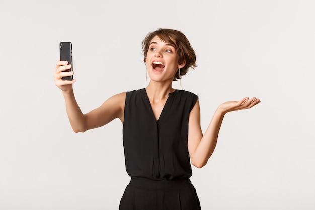 Привлекательная модная женщина, имеющая видеозвонок, демонстрируя что-то на камеру мобильного телефона, стоя на белом.